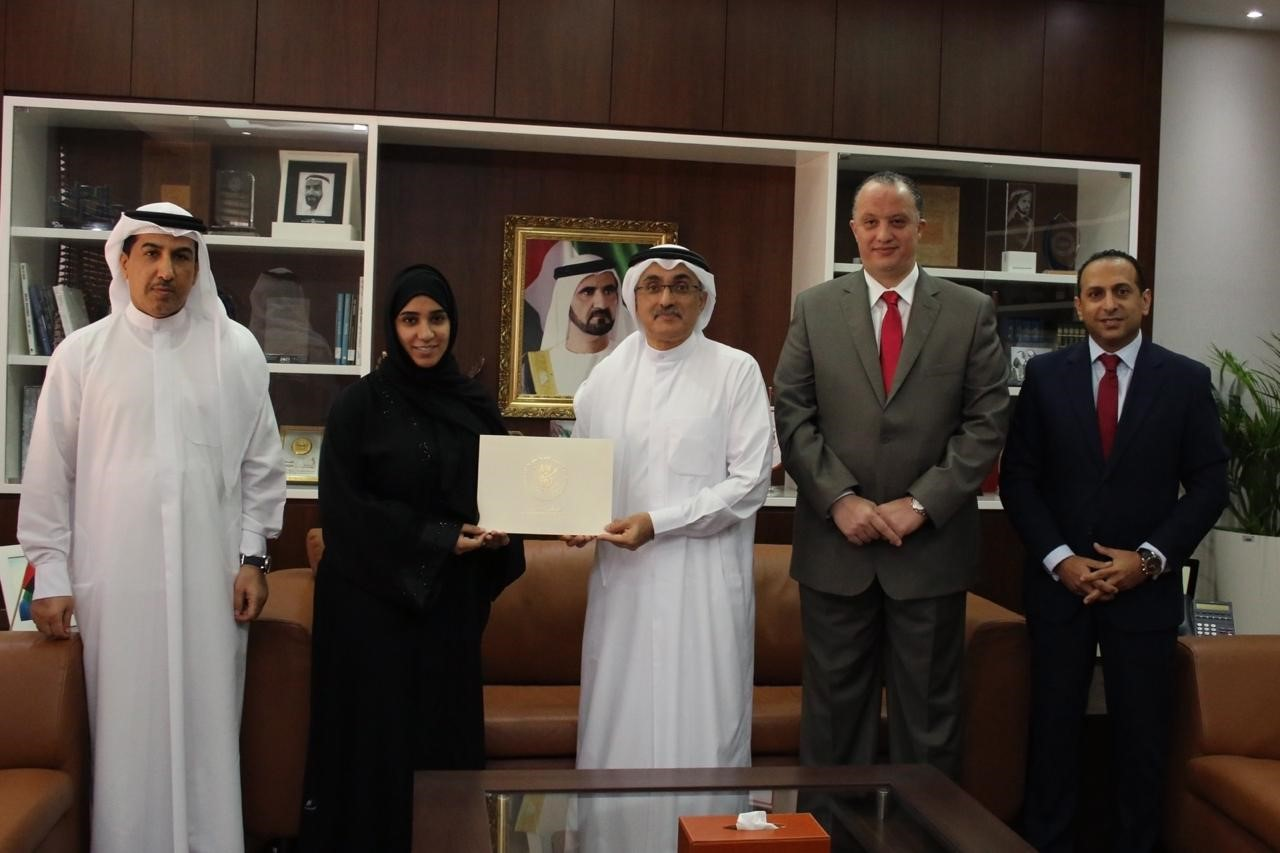 His Excellency Dr. Lowai Mohamed Belhoul, Director General of the Government of Dubai Legal Affairs Department, honours a group of employees as part of the